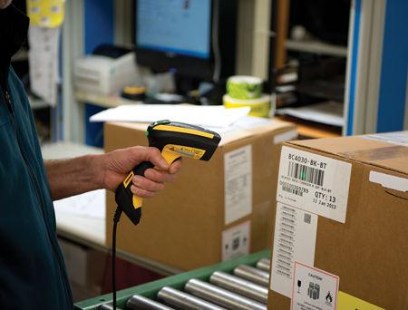 Un opérateur scannant un code barre sur un colis